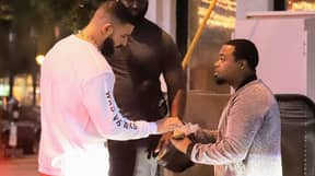 Drake Hands Hundred-Dollar Bills To Man In Street