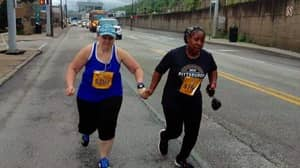 ​Marathon Runners Cross Finish Line Holding Hands As Final Competitors