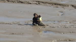 Beachgoers Get Stuck In Mudflats While Trying To Reach The Sea