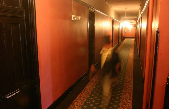 A ghoulish figure treads the hallways (actually just a dude in a top hat shot with a slow shutter speed). Credit: PA