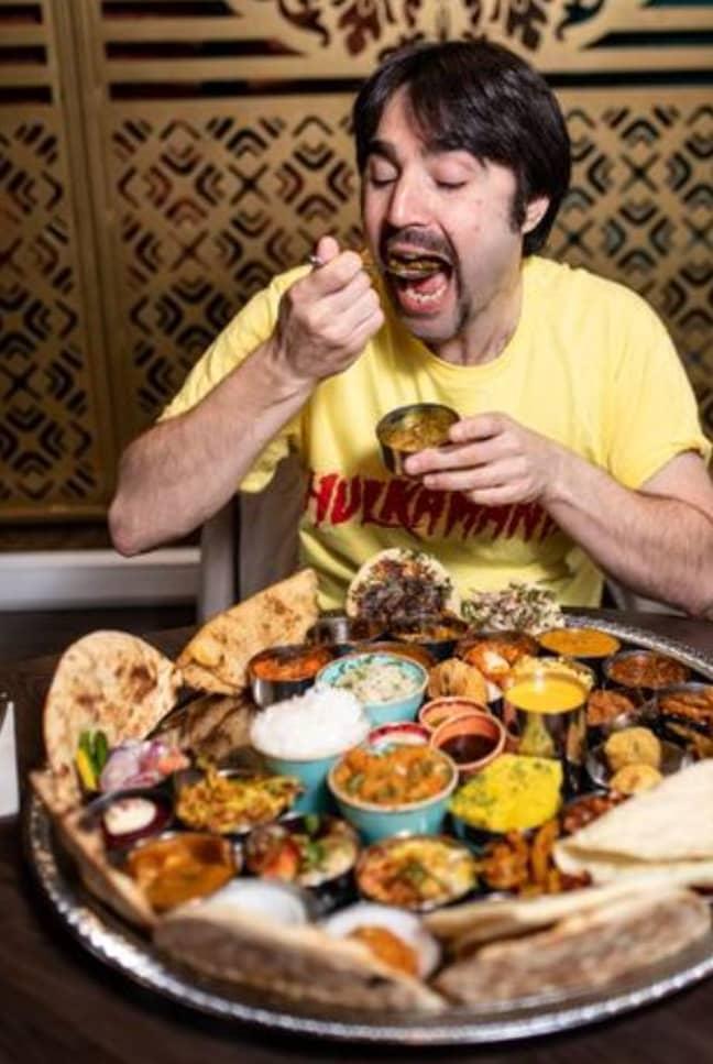Josh Sanders attempting the eating challenge. Credit: Mercury Press