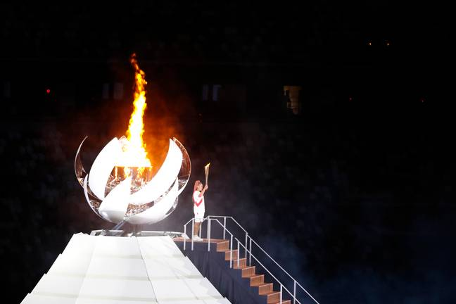 Naomi Osaka, tennis player for Japan, lights the Olympic flame at the Opening Ceremony. Credit: PA