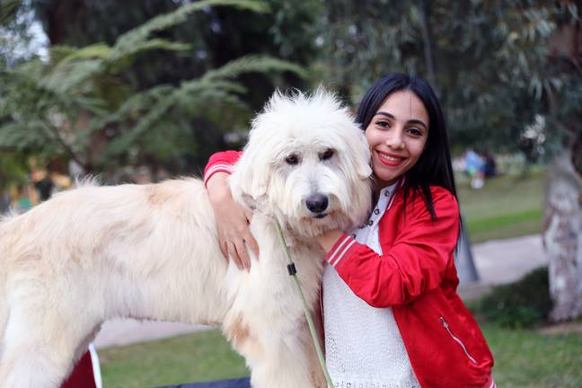 A girl poses with a dog during a pet carnival in Cairo, Egypt. Credit: PA