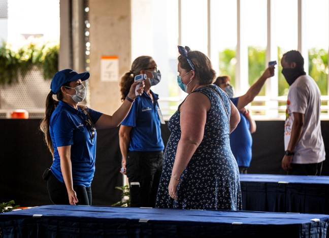 Visitors have their temperature checked before entering Disney Springs. Credit: PA