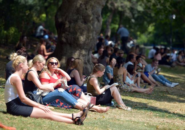 People seeking shade in the Victoria Embankment Gardens in London. Credit: PA
