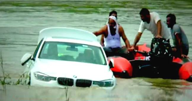 Local divers tried to get the car out of the river after it became stuck. Credit: Chauthi Duniya