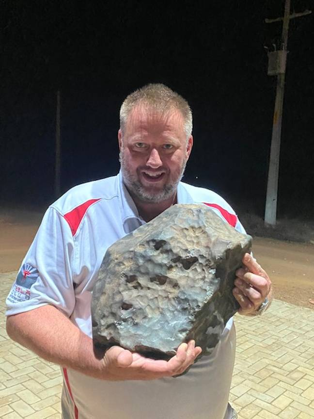Michael Farmer holding the 38.2kg piece of meteorite. Credit: Michael Farmer