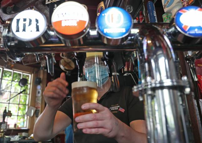 Barman Michael Fitzsimons wears PPE while pouring a pint during final preparations at The Faltering Fullback pub in North London. Credit: PA