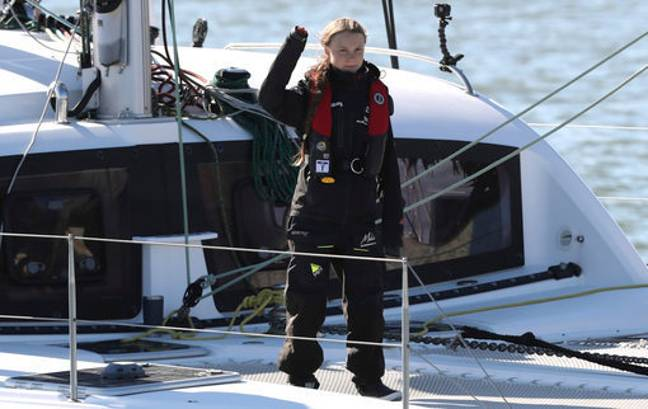 Thunberg waves as she arrives in Lisbon. Credit: PA