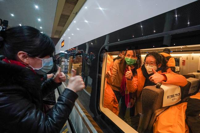 A relative encourages the medical staff at Nanjing South Railway Station on January 25 2020. Credit: PA
