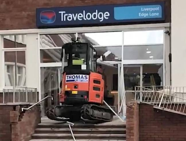 The driver rams the digger through the entrance. Credit: Twitter/@joefblue