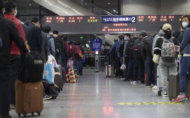 Passengers wait in line for train K81 at Wuchang Railway Station in Wuhan. Credit: PA