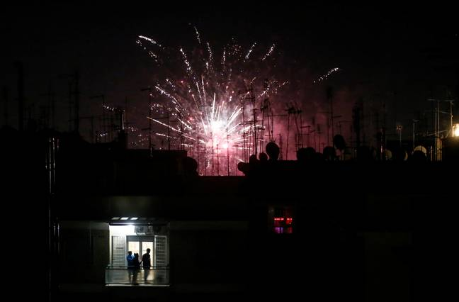 People on a balcony watch fireworks during the new year celebrations in Rome on Friday 1 January 2021. Credit: PA