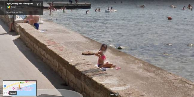 She clearly spots the Google Street view car coming and takes action to cover up. Credit: Google Maps
