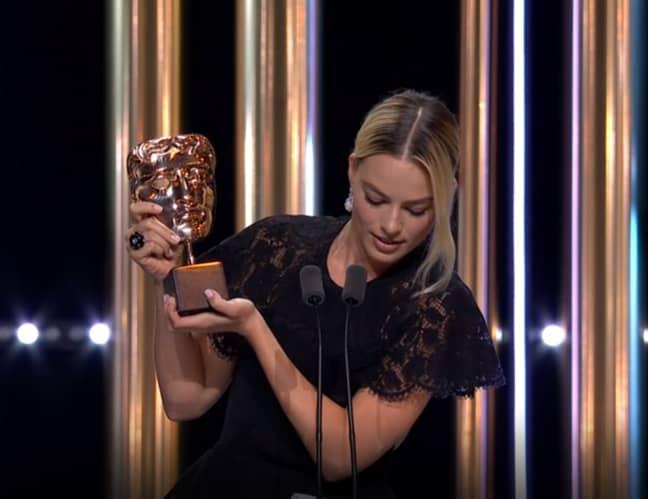 Robbie collecting Pitt's award. Credit: PA