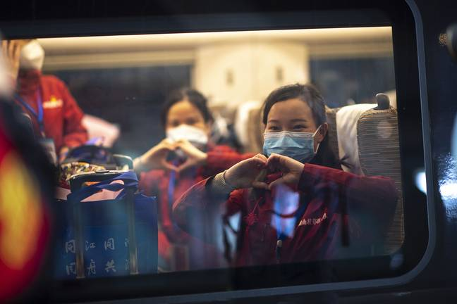 Medical staff from Hunan gesture on the train at a railway station in Wuhan. Credit: PA