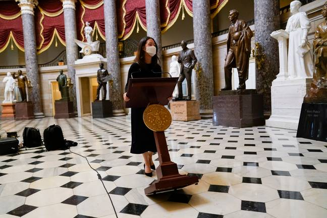The lectern that was stolen during last week's riot is wheeled trhough Statuary Hall. Credit: PA