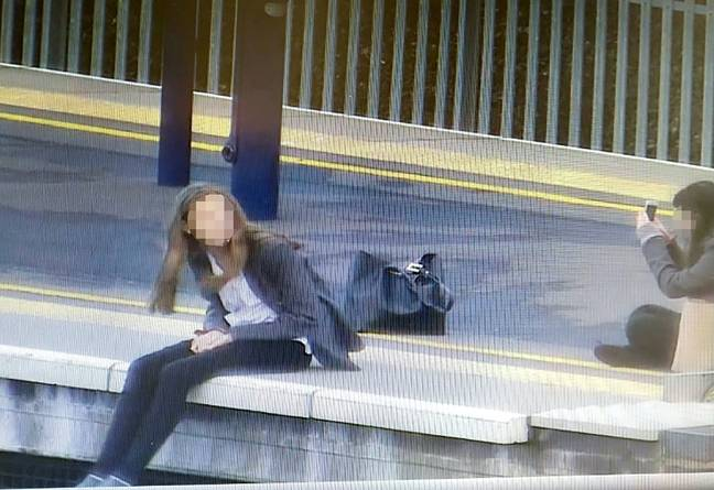 Trains needed to be delayed. Here one of the girls can be seen dangling her legs from the platform. Credit: SWNS