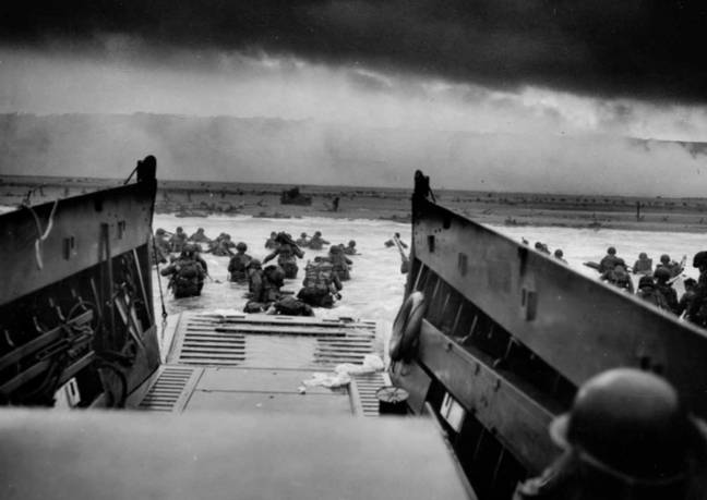 The soldier looks through the port hole as troops wade through the water to the beach. Credit: MEDIADRUMIMAGES / NARA
