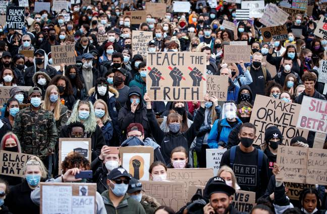 Demonstrators marching through Piccadilly Gardens in Manchester. Credit: PA