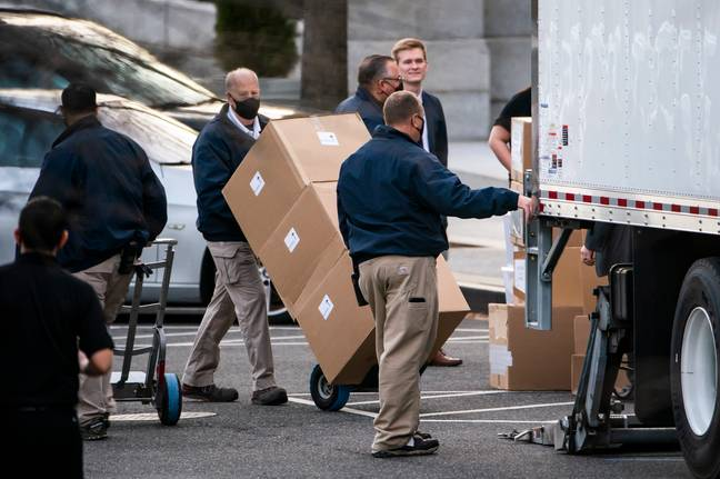 Workers move boxes onto a truck that were stacked on West Executive Avenue between the White House and the Eisenhower Executive Office Building. Credit: PA