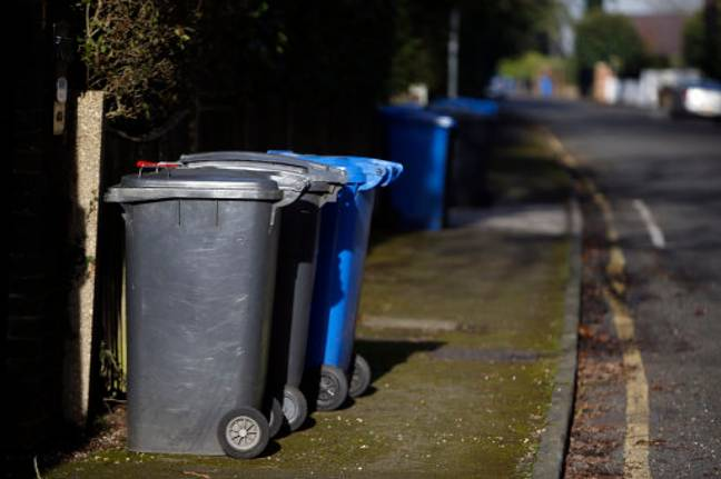 Rubbish and recycling bins line a street. Credit: PA