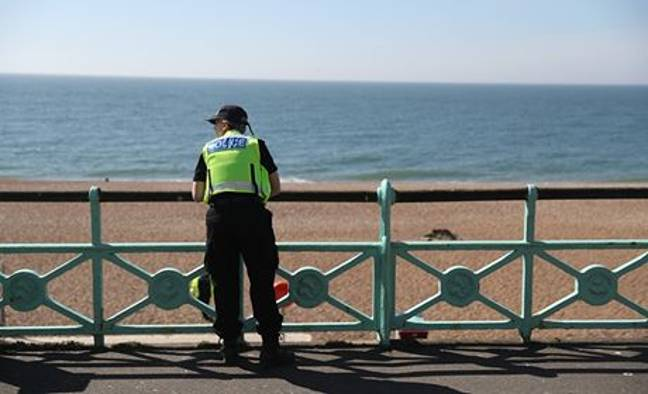 A police officer patrolling along Brighton Beach. Credit: PA