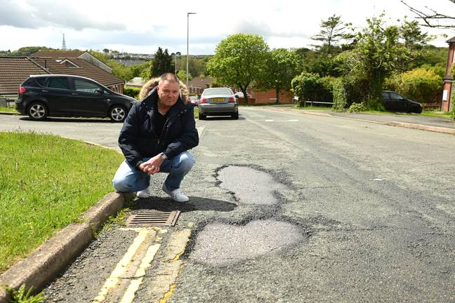 Al Mitchell indicating one of the potholes. Credit: Plymouth Live/BPM Media