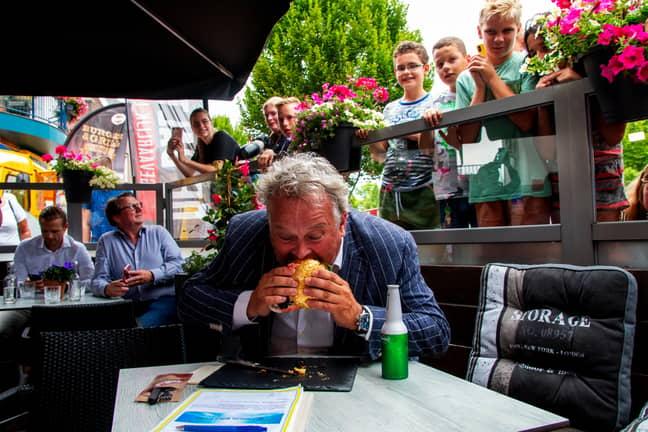 Rober Willemse taking a bite of the burger. Credit: De Daltons