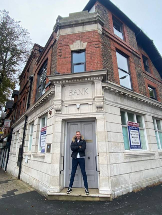 Adam outside the bank building where he was once rejected for a business loan. Credit: Adam Deering