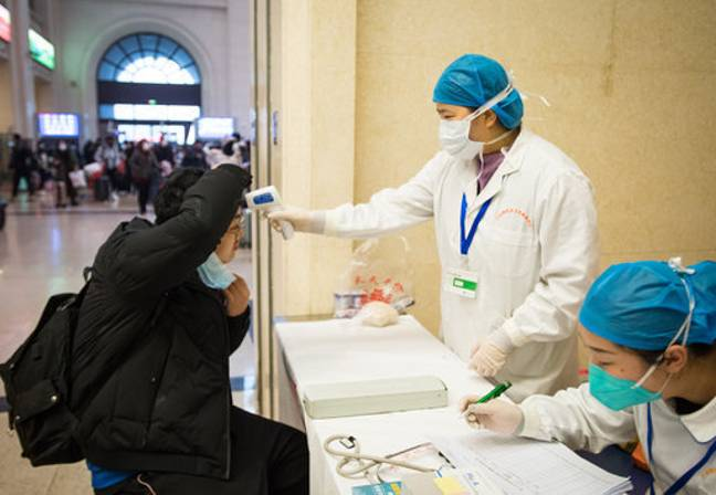 A medical worker takes a passenger's body temperature at Hankou Railway Station in Wuhan. Credit:  PA