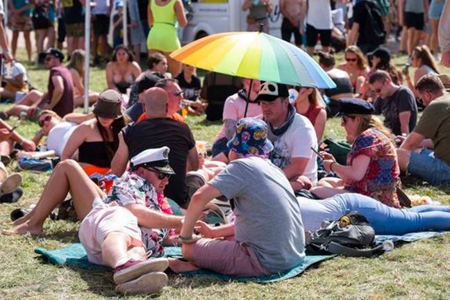 Festival goers were shading from the sun during the heatwave that struck during Glastonbury Festival. Credit: PA