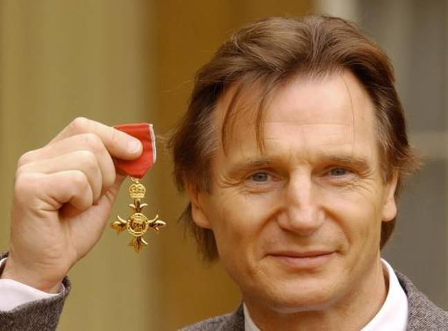 Liam Neeson holds his OBE in the forecourt of Buckingham Palace. Credit: PA