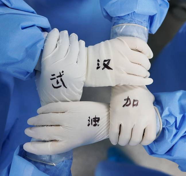 Nurses holding hands in surgical gloves with 'cheer up Wuhan' written on them. Credit: PA
