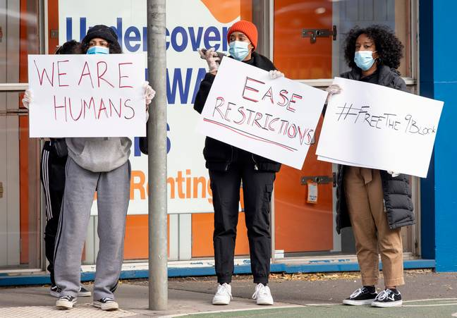 Women hold signs outside housing commission apartments in Melbourne. Credit: PA