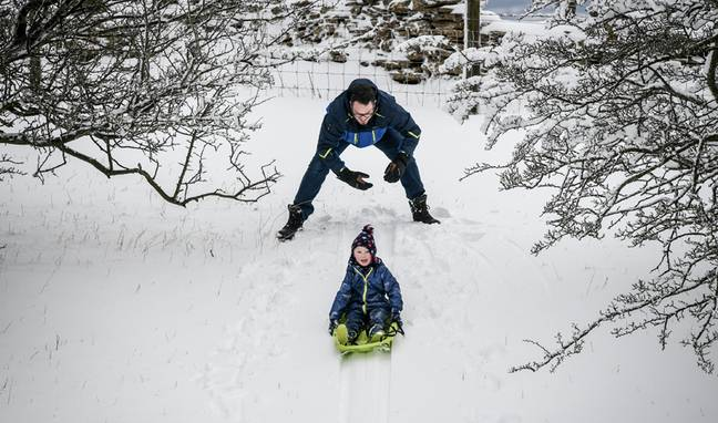 Kids make the most of the drifting snow on the Cotswold hills, Worcestershire. Credit: PA.