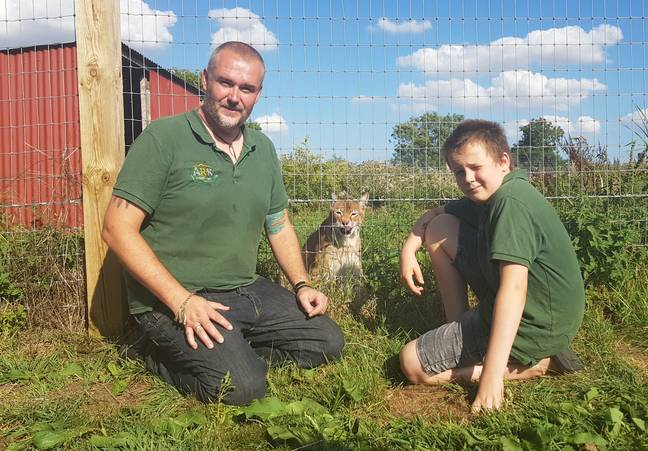 Jamie, pictured with son Josh, takes care of several wild cats and reptiles. Credit: Supplied