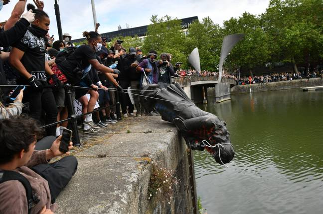 Protesters throw statue of Edward Colston into the Bristol harbour. Credit: PA