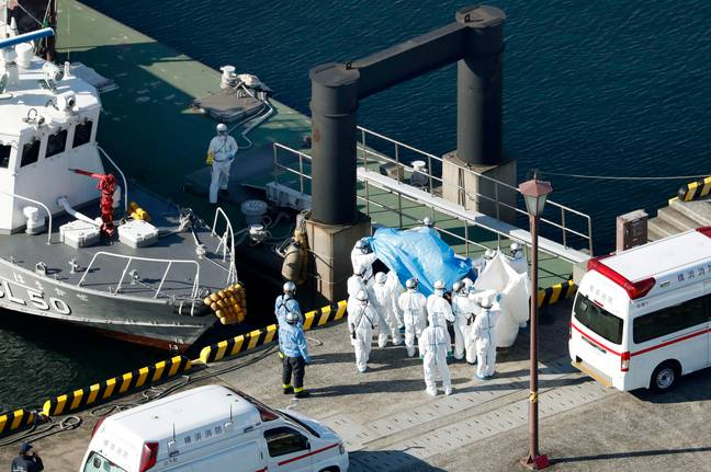 A passenger who tested positive is led away from the ship. Credit: PA