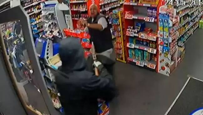 The shopkeeper using a magazine to defend himself... from a gun. Credit: Derbyshire Constabulary