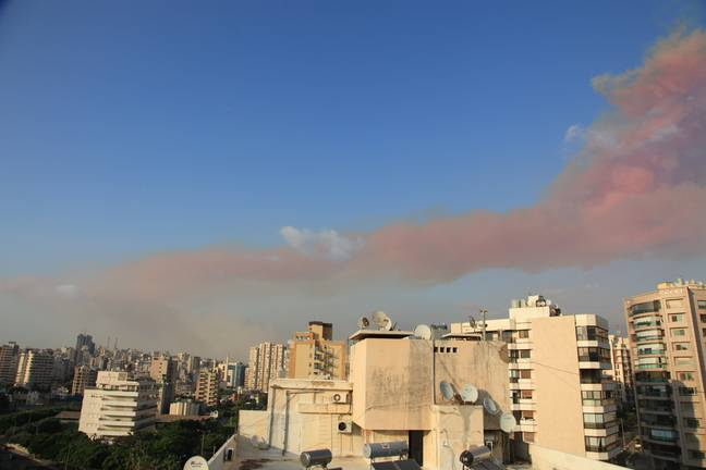The large plume of pink smoke rises over Beirut. Credit: PA