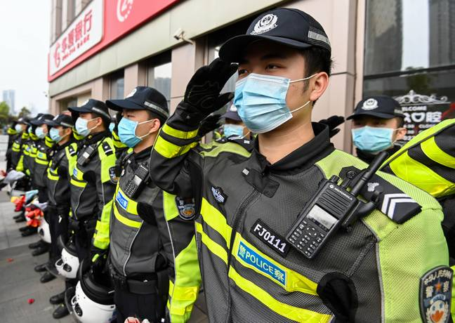 Policemen salute to medics from Guangdong Province before departure in Wuhan. Credit: PA