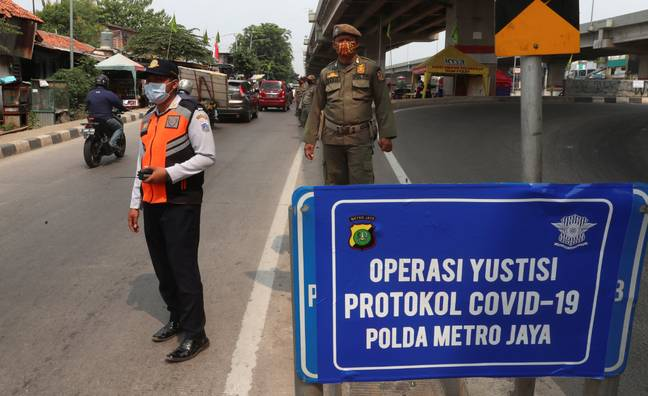 Officers stand guard at a police check point as the large-scale restriction is imposed to curb the spread of the coronavirus outbreak in Jakarta, Indonesia. Credit: PA