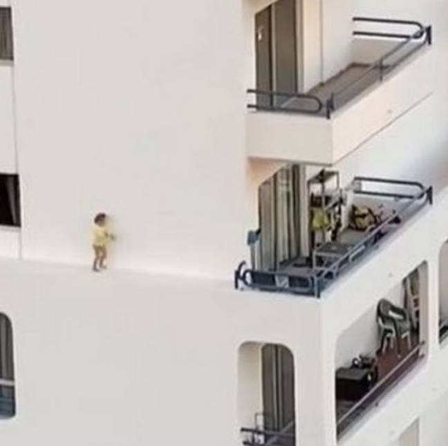 The small toddler can be seen running across the narrow ledge of an apartment complex.