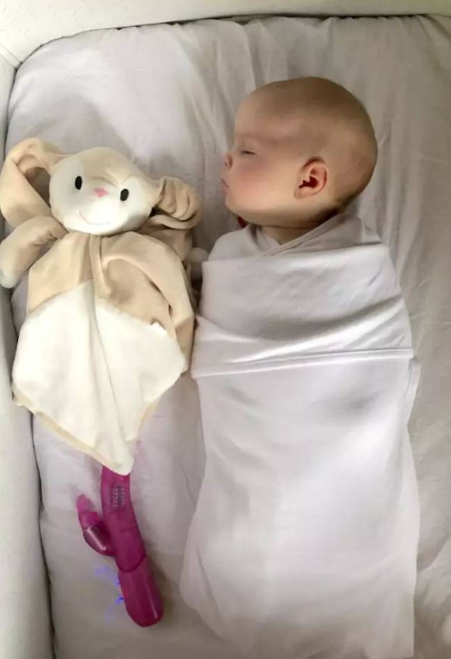 Baby Lucie with her unconventional sleeping aid. Credit: StoryTrender