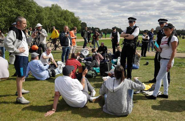 Police approach people protesting the lockdown in Hyde Park, London. Credit: PA