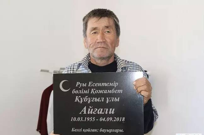 Aigali Supugaliev posed with his own gravestone and doesn't he look delighted to be alive? Credit: Ak Zhaiyk/east2west news