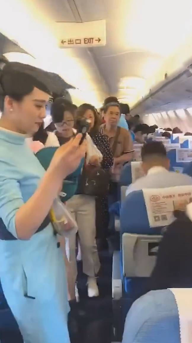 Cabin crew and confused passengers inside the delayed Xiamen Airlines flight. Credit: AsiaWire/Weikandian