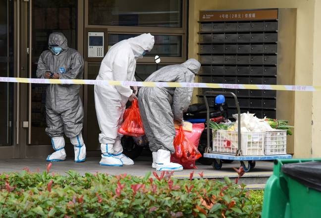 Staff members in protective suits deliver living materials for residents in a sealed-off neighbourhood in Qingdao. Credit: PA