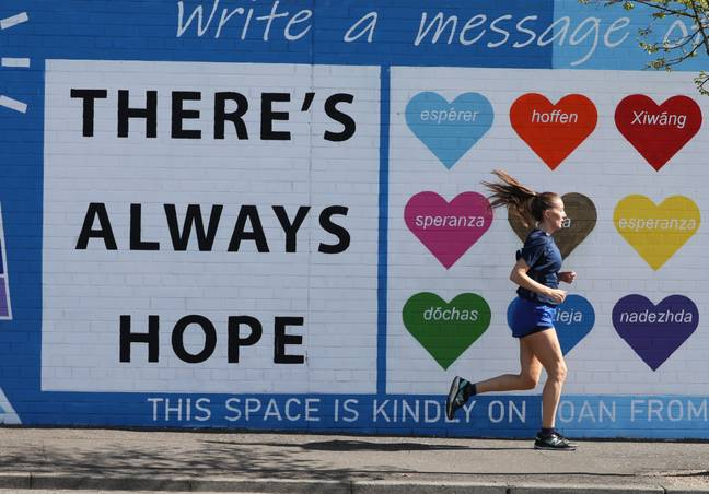 A woman runs past a mental health mural on the Falls road in west Belfast in April. Credit: PA
